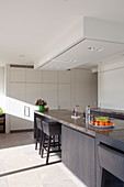 Island counter, barstools and white floor-to-ceiling fitted cupboards in elegant kitchen