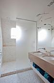 Waschtisch mit Doppelwaschbecken und Duschbereich mit Trennwand im Badezimmer mit Kieselsteinbelag