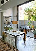 Esstisch mit verschiedenen Stühlen vor offener Fassade zur Terrasse