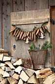 Garland of fir cones on wooden shutter above stacked firewood