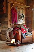 Vintage Ledersessel und weihnachtliche Dekoration in rustikaler Holzhütt