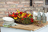 Arrangement of red and yellow tulips, narcissus, ranunculus, mosses and twigs on table