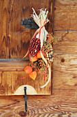 Hanging arrangement of multicoloured corncobs, physalis and rose hips