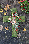 Mossy cross decorated with Gaultheria berries, poppy seedheads, silver ragweed and rose hips