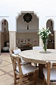Runder Tisch mit Natursteinplatte und Stühlen in der Lobby im Hotel Ryad Dyor (Marrakesch, Marokko)