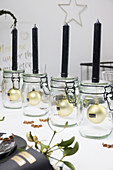 Black candles on mason jars with Christmas-tree baubles inside