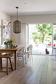 Rustic wooden table and chairs in dining area with French windows