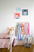 Coat pegs and laundry sack next to bed in child's bedroom