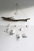 Handmade mobile with plaster figures suspended from branch in child's bedroom