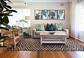 Rattansessel, Couch und Couchtisch auf Teppich mit geometrischem Muster und botanische Drucke an der Wand im Wohnzimmer