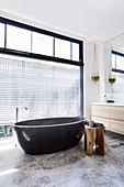 Oval freestanding bathtub in modern bathroom with window front