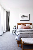 Single bed in a bright bedroom with gray carpeting