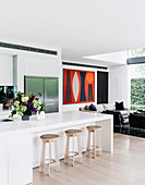 White, open kitchen with kitchen counter and bar stools