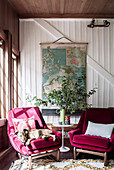 Pink armchair with dog and side table in front of window