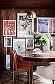 Table with chairs and arc lamp in the dining room, pictures on a wood-clad wall