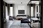 Großzügiges Schlafzimmer mit Himmelbett, Kleiderbank, silberfarbenem Teppich und Sofagarnitur