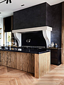 Designer kitchen with black wall and wood and granite island