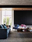 Blaues Polstersofa, Stuhl in Fell-Optik und Couchtisch in offenem Wohnraum