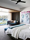 Doppelbett, Gemälde und blaues Sofa in großzügigem Schlafzimmer mit Glasfront