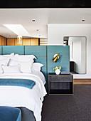 Doppelbett und Nachttisch an blauem Paneel als Bettkopfteil und Raumteiler im Schlafzimmer