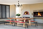 Wooden table with benches, pizza oven and barbecue in dining area