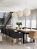 Upholstered chairs and spherical lamps in elegant dining area with glass wall