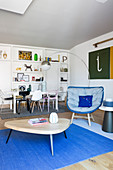Coffee table, easy chair with blue cover, arc lamp, dining table with various designer chairs and floor-to-ceiling fitted shelving