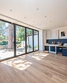 Heller Raum mit Fensterfront zur Terrasse und Eckbank um den Tisch