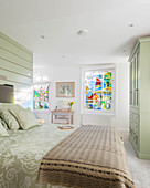 Pale green furnishings in bedroom with stained-glass windows