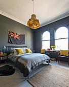 Schlafzimmer mit grauen Wänden und senfgelben Akzenten