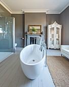 Wohn-Badezimmer mit Sofa, ovaler Wanne und offenem Kamin