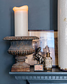 White candle in metal urn and vintage-style ornaments