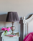 Pink roses and vintage-style lamp on bedside table