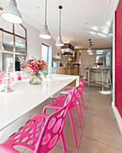 Hot-pink chairs at dining table in sunny kitchen-dining room