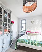 White bed in light-flooded bedroom