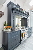 Mirrored wall above cooker in grey country-house kitchen