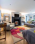 Graue Polstermöbel um bunten Teppich im Wohnzimmer