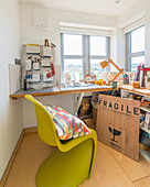Grüner Designerstuhl am Eckschreibtisch unterm Fenster