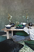 Green cushions on floor around low table with place settings