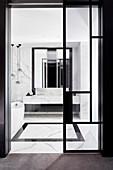 Blick durch Glastür ins Badezimmer mit Marmorfliesen