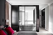 Blick vom Schlafzimmer durch Glastür ins Badezimmer mit Designerbadewanne