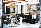 Black granite kitchen island, dining table and classic chairs in open living space