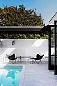 Classic chairs on a white, brick terrace with pool
