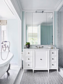 Wall mirror over white vanity and free-standing bathtub in elegant bathroom
