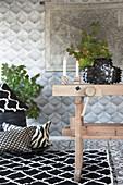 Rustikaler Holztisch, schwarz-weißer Teppich und Kissen