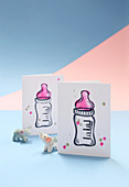 Hand-made invitation cards to a baby shower with a baby bottle motif