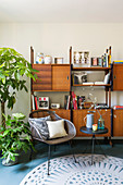 Chair and side table in front of retro shelving and houseplant