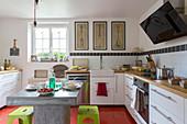 Betontisch mit bunten Hockern vor L-förmiger Küchenzeile