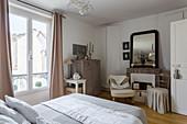 Schlafzimmer in Naturtönen mit Doppelbett, Kommode und stillgelegtem Kamin