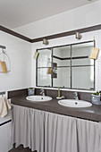 Washstand with twin sinks and curtained front in bathroom